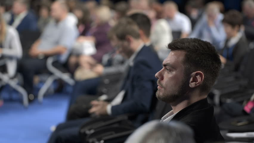 Crowded congress in marketing center indoors. Businesspeople looking economy information for leadership or cooperation strategy of young banking company. Adult listener or spectator sitting on chair | Shutterstock HD Video #1020788593