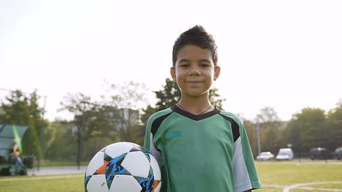 Cute little boy with soccer ball in the hand looking to the camera on the football field on the sunshine background.