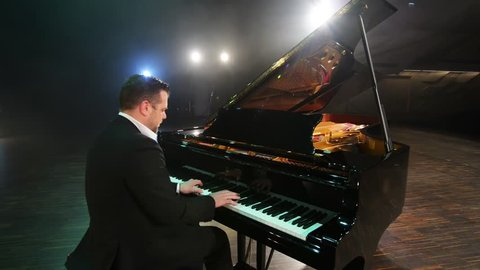 Mature bearded caucasian attractive male pianist in dark suit and classic shirt plays beautiful black grand piano on big stage in concert hall with dimmed light.