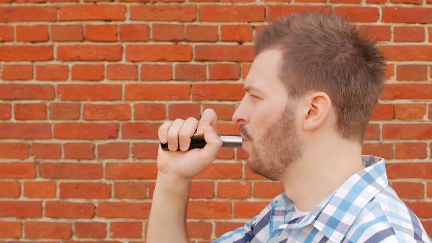 Handsome stylish man smoking vap against a brick wall and looking into the camera, slow-mo, fashionable   Shutterstock HD Video #1020878233