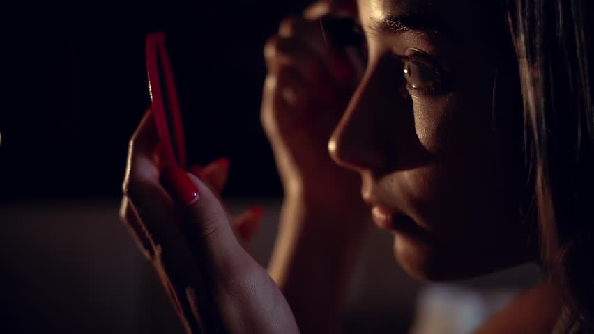 In dark face woman applying makeup  #1020887023