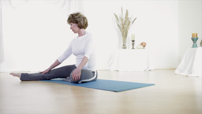 A Mature Physically Fit Woman Sitting On A Bright Shinny Wooden Floor Doing  Yoga To Stretch