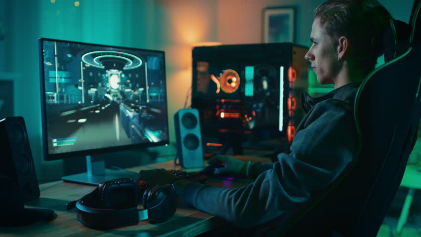 Concentrated Gamer Playing First-Person Shooter Online Video Game on His Powerful Personal Computer. Room and PC have Colorful Neon Led Lights. Cozy Evening at Home. | Shutterstock HD Video #1020930943