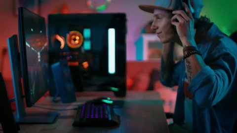 Gamer Puts His Headset with a Mic On and Starts Playing Shooter Online Video Game on His Personal Computer. Room and PC have Colorful Neon Led Lights. Young Man is Wearing a Cap. Cozy Evening at Home.