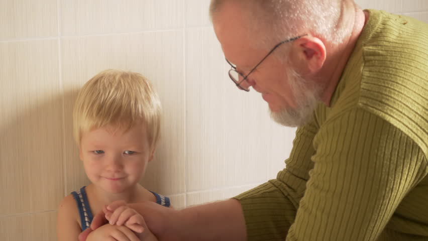 Happy elderly man washes his hands on tap from his hand and face to his little son and wipes him with towel. father takes care of child, Helps and takes care of him. Family joy, hygiene   Shutterstock HD Video #1020976723