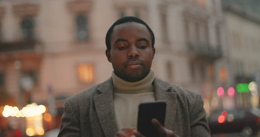 Portrait of the African American attractive young man in the coat using and texting on his smartphone in the city on the twilight, then smiling to the camera. Close up. Outdoors. | Shutterstock HD Video #1021027093