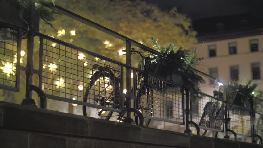 Bicycles on embankment near the canal of Strasbourg, France. Bike rim at night, lights in the background. Urban lifestyle. | Shutterstock HD Video #1021043353