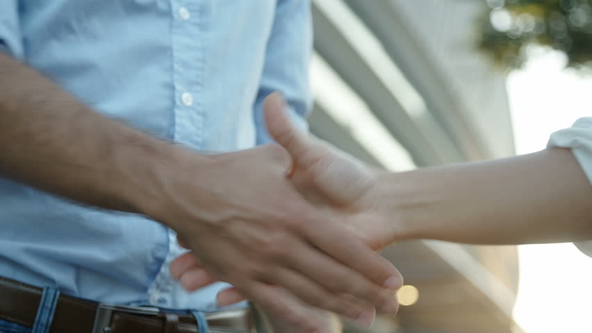 Close up slow motion footage of two business people shaking hands. Manager and his assistant shaking hands after important interview. Static shot. Successful people, business concept.