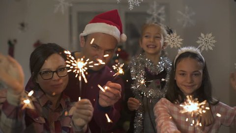 Happy young sparklers - parents and daughters holding and waving bengal fire like best wishes for new year or merry Christmas, decorated snowflakes, family holidays, xmas, x mas, scene in slow motion.