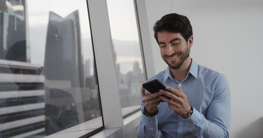 Good looking white ma man at office smiling after sending voice message using his smartphone. Happy Handsome Caucasian Businessman use his phone to send message with app. With Copyspace. | Shutterstock HD Video #1021089613