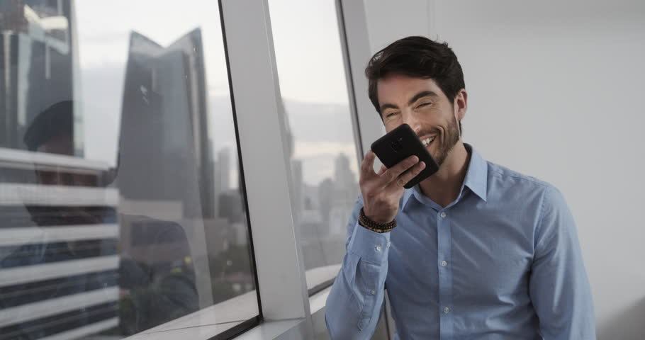 A young good looking man at office smiling after sending voice message using his smartphone. Happy Handsome Caucasian Businessman use his phone to send message with app. Technology usage young people   Shutterstock HD Video #1021089613