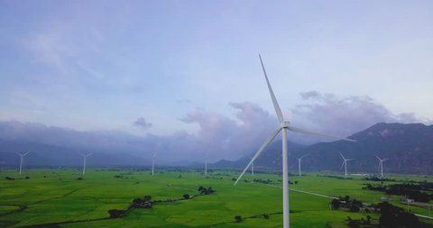 Wind turbine farm and agricultural fields on blue sky. Turbine green energy electricity or wind turbine in a green field - Energy Production with clean and Renewable Energy. Phan Rang, Vietnam
