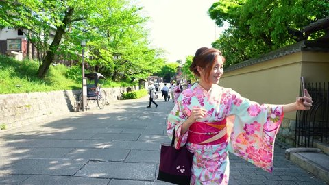 Kyoto, JAPAN - APRIL 20, 2018: young beautiful japanese women in floral kimono dress walking outdoor on street. travel lady in traditional clothing using cellphone joyful with pulled rickshaw in back
