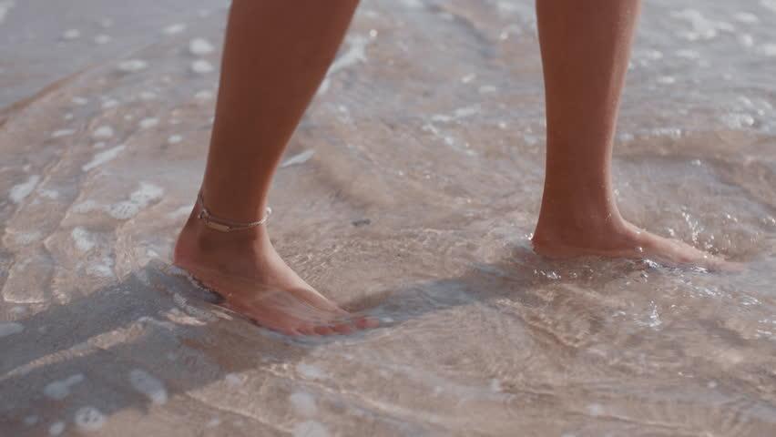 Close up woman feet walking barefoot on beach enjoying waves splashing gently female tourist on summer vacation | Shutterstock HD Video #1021159813