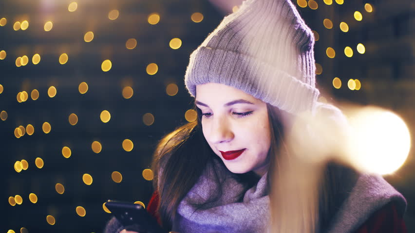 Lonesome young woman on the smartphone for Christmas 4K. Portrait sliding shot of young woman in focus wearing winter clothes and surrounded by decorative lights. | Shutterstock HD Video #1021189843