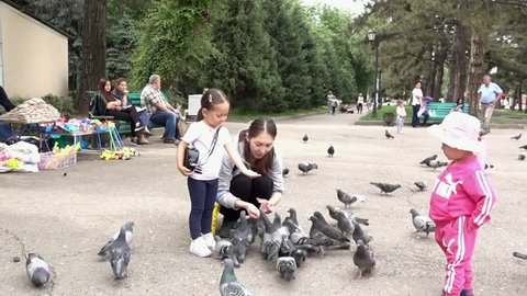 Almaty, Kazakhstan - 05 31 2017: Almaty, Kazakhstan / May 31, 2017 - Pigeon flies into girls hand in park