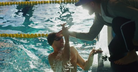 Professional swimmer is encouraged by his coach for new record achievement. Shot with RED Camera in 8K. Concept of sport, swimming pool, competition, fitness.