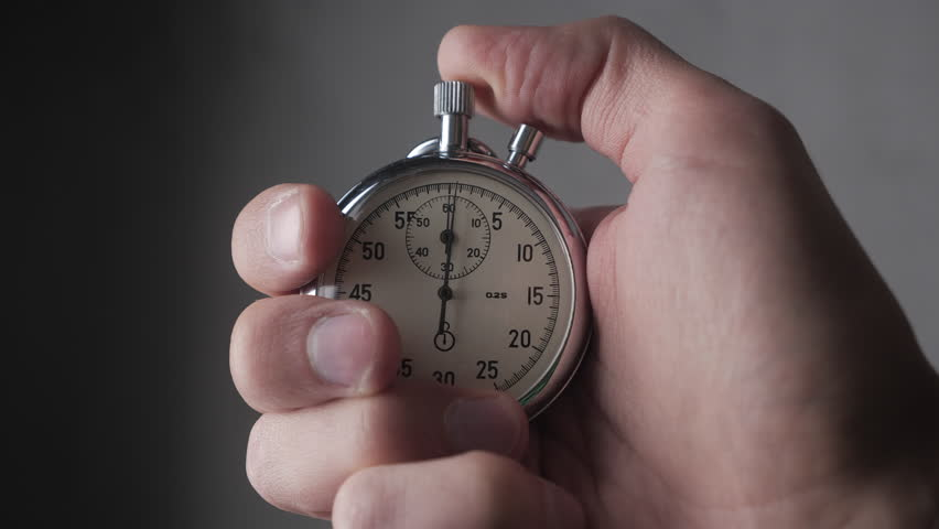 Close-up of one person starting up a stopwatch at grey background. 4K, 10 BIT, 4:2:2. | Shutterstock HD Video #1021289143