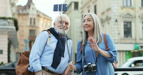 Caucasian old smiled couple of tourists standing in the city center with a smartphone on the selfie stick and having a videochat ot taking photos. Outside.
