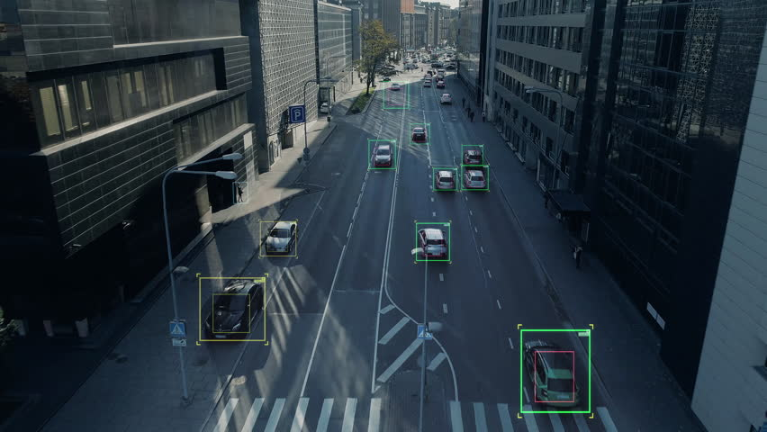 Aerial Drone Shot: Autonomous Self Driving Cars Moving Through City. Concept: Artificial Intelligence Scans Cars and Pedestrians, Following Movement and Showing Data. | Shutterstock HD Video #1021307803