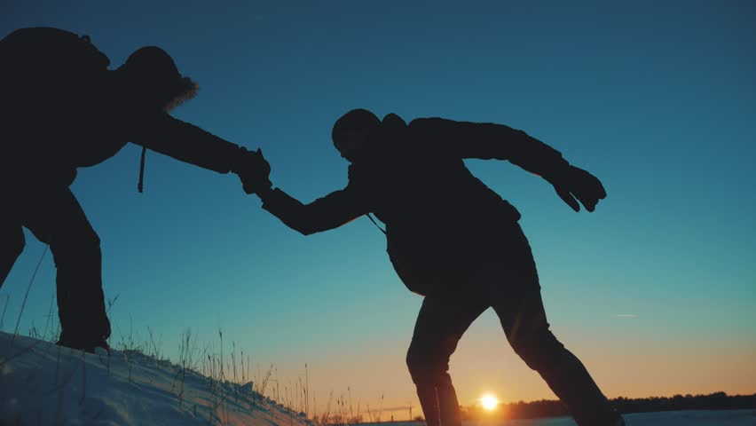 Teamwork business travel silhouette concept. two hikers winter snow tourists climbers climb to the top of mountain . lifestyle overcoming hardships the path to victory, teamwork, important points in | Shutterstock HD Video #1021321303