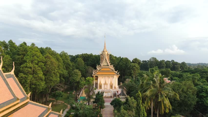 Aerial drone view fly down holy walkway flanked by ornate poles, then rise and settle on large Buddhist pagoda in rural Southeast Asia. | Shutterstock HD Video #1021404703