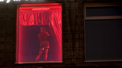 On the street of Amsterdam's red-light district, a woman in uniform dances a striptease. Easy erotic girls in the window with red neon. Striptease for men in a nightclub. Nightlife for adults 4k.