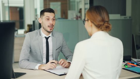 Smiling young man recruiter is talking to young woman successful candidate then shaking her hand during job interview in office. People and work concept.