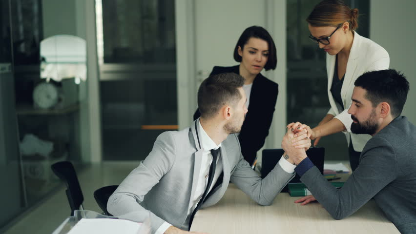 Bearded young people office workers are having fun practising arm wrestling while women are watching and supporting them then doing high-five and clapping hands. | Shutterstock HD Video #1021442173
