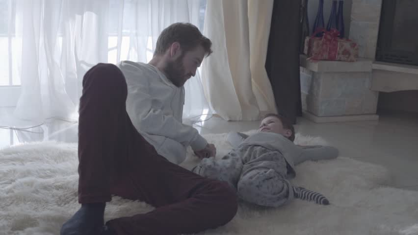 Bearded father talks with the child. Bearded dad and his son lying on the white carpet. Father agrees with the child. Father-child relationship. | Shutterstock HD Video #1021493143