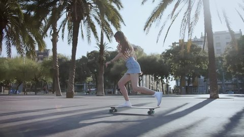 Young beautiful female hipster skater long blond hair girl in mini jeans skirt riding on beach street with palms on skateboard or longboard in summer hot day. Enjoying skateboarding and active sport