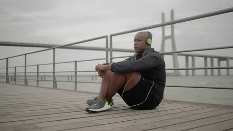 Relaxed african american man in headphones on wooden pier. Bald man sitting with crossed legs and looking around. Relaxation concept
