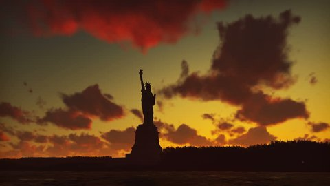 Statue of Liberty at sunrise, with the new York skyline and sunrise, sky with clouds in the background.