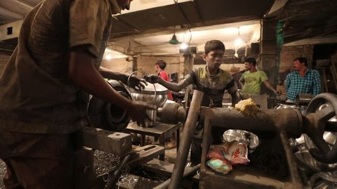 DHAKA, BANGLADESH - DECEMBER 07, 2018: A young childlabour worker is working in a sweatshop in Bangladesh producing metal or aluminium pots under dangerous circumstances