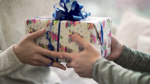 Close-up of man passes gift to woman. Close-up guy gave his girlfriend Christmas or new year's gift. Festive winter atmosphere