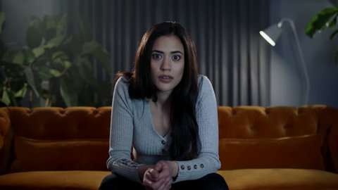 Shocked and surprised reaction from a woman watching TV at home. Camera pushes in towards her reaction. Shot on ARRI Cinema Camera and lenses in 4K (UHD).