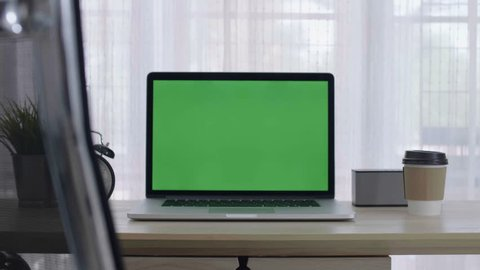 4K Green screen of laptop computer set on working space in cozy office, Zoom in shot