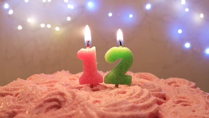 Burning Birthday Candle On A Cake Number 12 Blow Out At The End Color Blurred Background