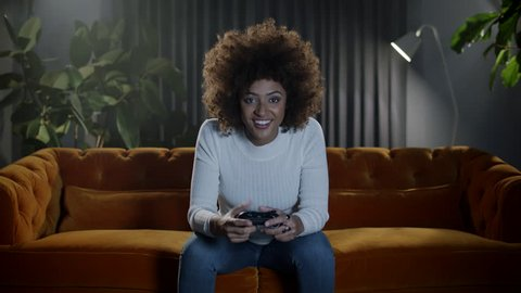 Girl gamer playing video games at home.