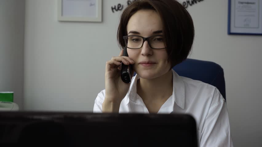 Close-up of secretary with smile talking on phone. Attractive young woman talking on phone in office | Shutterstock HD Video #1021605343