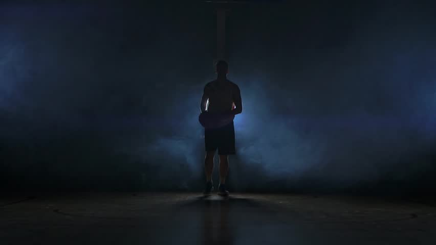 Basketball player goes straight to the camera in a dark room with a backlit back in the smoke looking at the camera in slow motion. Steadicam | Shutterstock HD Video #1021620493