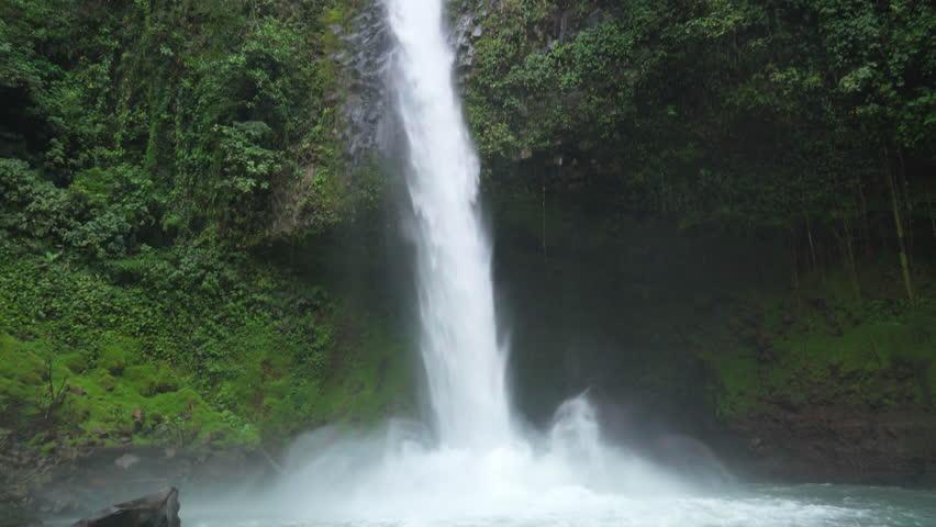 La Fortuna Waterfall flowing in the lush Costa Rica rainforest, Tilt Shot