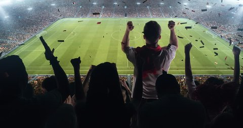 Group of cheering fans watch a soccer championship on stadium. Their team wins and everybody are celebrating this event. People are dressed in casual cloth. Colourful confetti flies int the air.