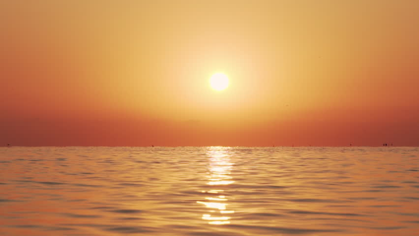 Sea surface with small waves against the backdrop of sunrise of sun slow motion. Large disk of sun rises above sea, solar path on water. Golden light of sea panorama. Relax