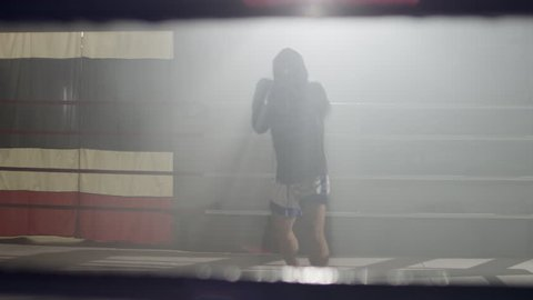 Muay Thai fighter in hoodie throwing punches and kicks at camera, shadow boxing, training in the middle of a foggy boxing ring backlit with flares in the background, wide shot