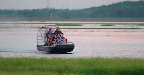 ORLANDO, FLORIDA circa Dec 2017 - An airboat carries tourists through a central Florida swamp and grassy wetlands in search of wildlife at sunset.