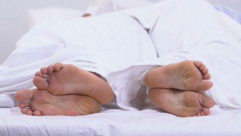 Feet of couple lying in bed under duvet, calluses and corns, fungal disease