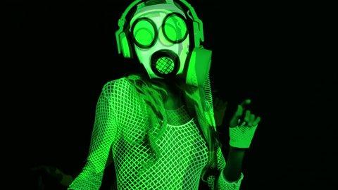 uv fluorescent female gogo dancer dances wearing a gasmask