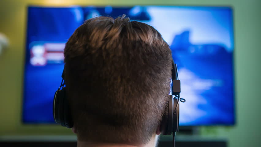 Gamer Guy w/ Headphones. Male plays a videogame while wearing headphones.