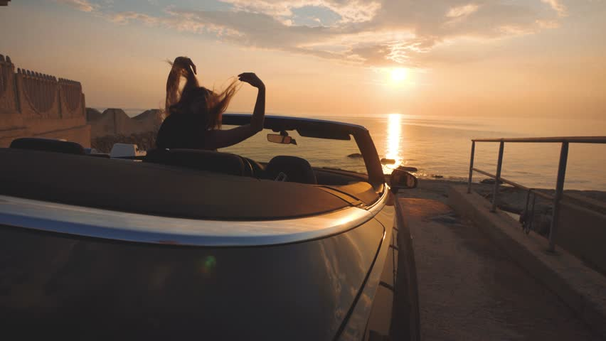 Girl dances on driver place in cabriolet car. Gentle colors of sunset over sea | Shutterstock HD Video #1021949323